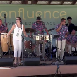 Members of Orquesta Mayor preforming on an outdoor stage for