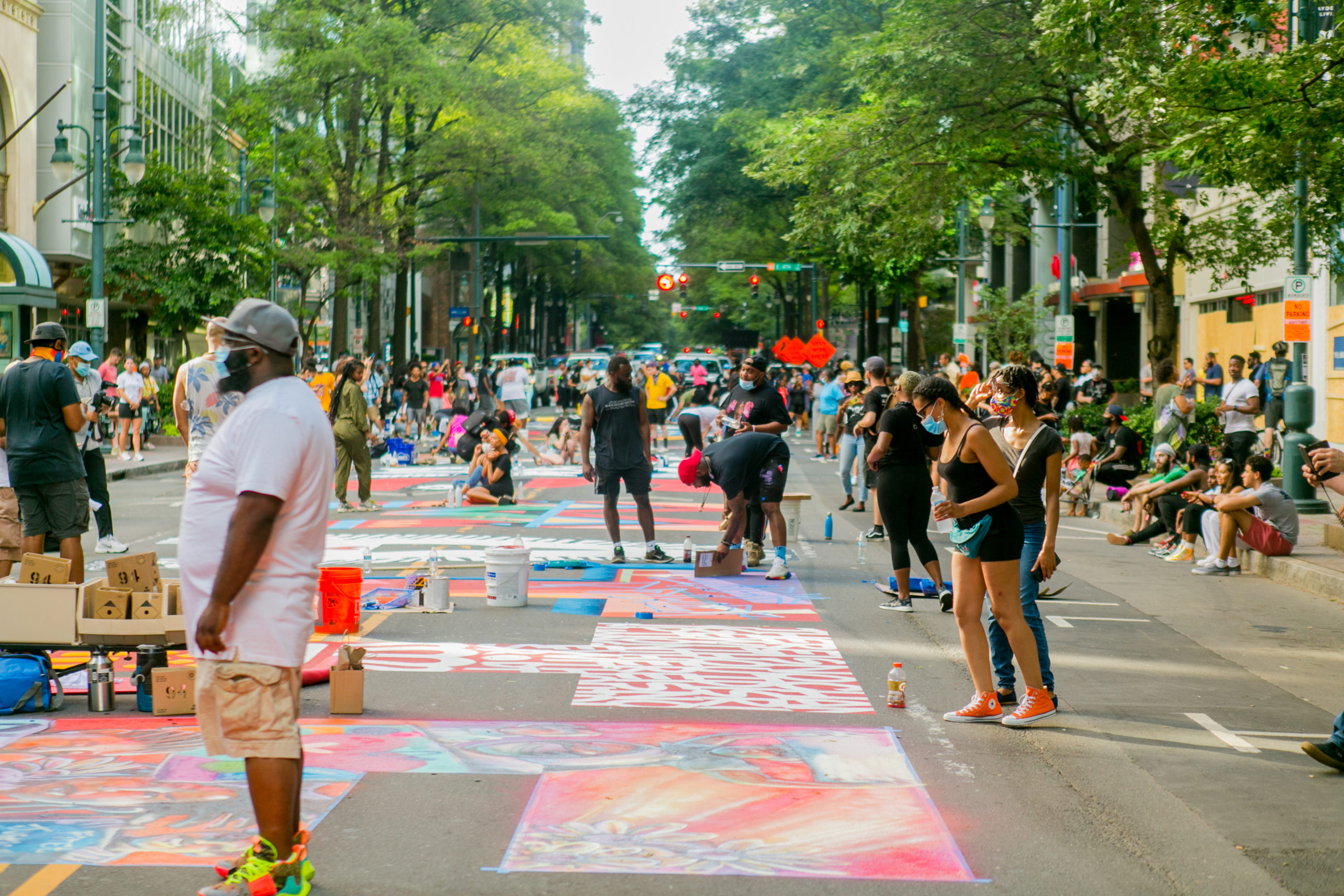 "A group of people watching artists paint the ""Black Lives Matter"" mural on South Tryon Street"