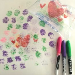 Markers and a plastic bag sitting next to a piece of paper decorated with dots and hearts transferred from the plastic bag.