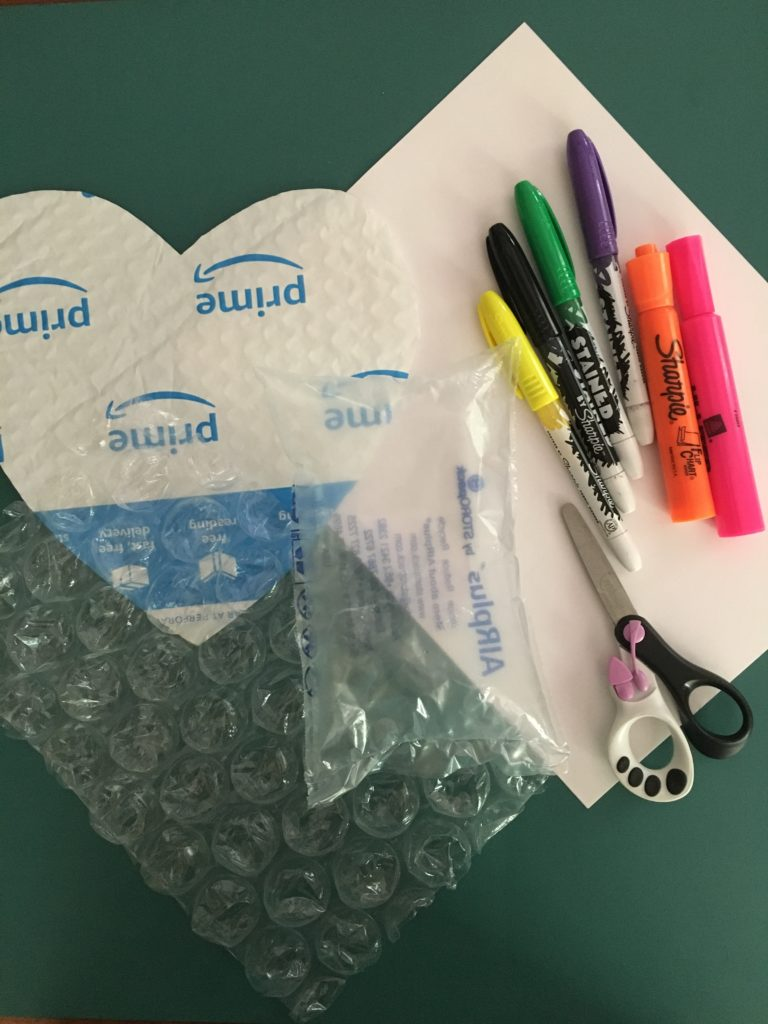 Supplies listed for this project grouped together on a table: bubble wrap, markers, scissors, paper, plastic bag