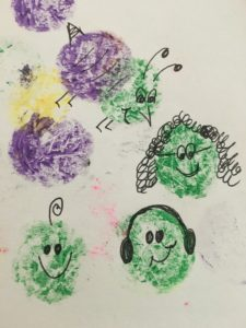 Multicolor paint dots on a piece of paper with pen drawings on top of the paint. With the pen marks, the dots have been turned into faces and a bumblebee