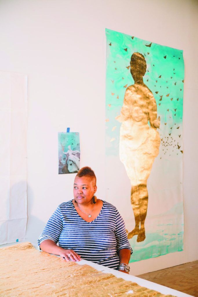 Stacy Lynn Waddell sits at a table in her studio, looking to the side of camera. A large work of art by Waddell is hanging behind her. The art depicts a woman covered in gold, with gold butterflies surrounding her.