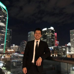 Joseph Gallo standing in front of the city of Charlotte's skyline